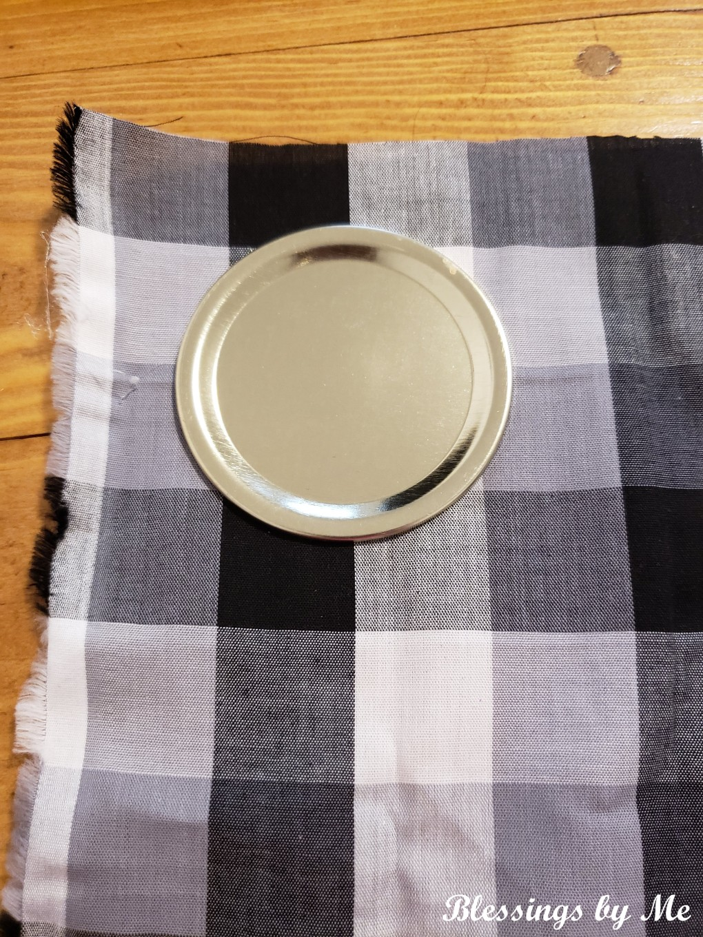 place the mason jar lid on the fabric and cut out a square